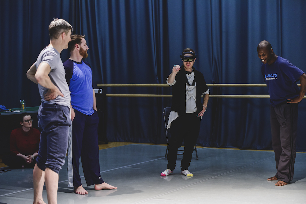Trio of dancers stood up and taking instruction from the artistic director wearing AR equipment